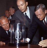Buzz Aldrin, Michael Collins & Neil Armstrong looking at a sample of moon rock that they had brought back to earth with them
