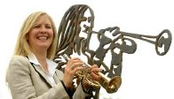 Alison Balsom next to her statue at the junction of Green Street and Melbourn Road in Royston.