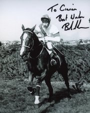Photo signed by Bob Champion showing Aldaniti jumping the last fence in the 1981 Grand National