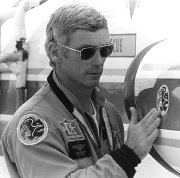 Gene Cernan in 1972 sticking an Apollo 17 emblem on his NASA T-38 before leaving for the Apollo 17 mission.  Patches from all 3 of his missions are on his jacket.