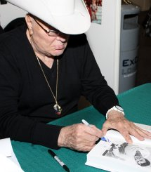 Tony Curtis signing a copy of his autobiography at London Expo in May 2009