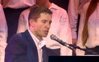 Lee Evans sings at the piano with a choir backing