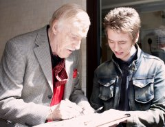 Bruce Forsyth signs a lobby card for Ciaran Brown