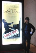 Lang Lang with a poster indicating a sold out concert