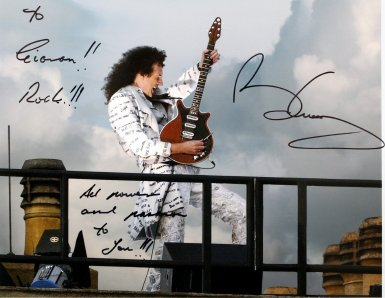 Brian May signed photo. It shows him playing the National Anthem on the roof of Buckingham Palace in 2002