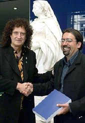 Brian May hands in his PhD thesis to Professor Paul Nandra at Imperial College