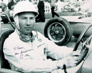 Photograph signed by Sir Stirling Moss showing him in his Maserati before the 1954 Belgian Grand Prix in which he finished third