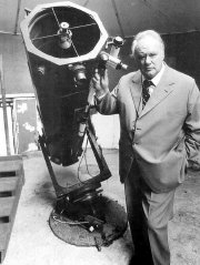 Sir Patrick Moore with his reflector telescope in his observatory at Farthings