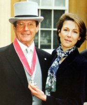 Roger Moore with his daughter Debbie after receiving his CBE in 1999