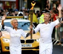 Jayne Torvill and Christopher Dean carry the Olympic Torch through Nottingham in 2012