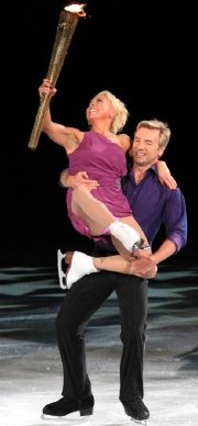 Jayne Torvill and Christopher Dean skate with the Olympic Torch at Nottingham's National Ice Centre in 2012