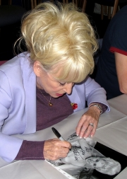 Barbara Windsor signing a photograph